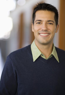 A man smiles to show how Dental Crowns from our Seattle dentist can restore your smile with a natural look.