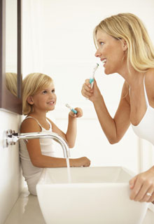 A mother teaching her daughter proper dental hygiene
