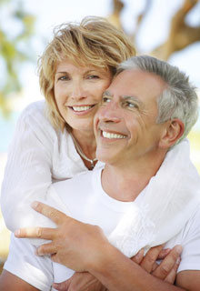An older couple hugging and smiling to show or Restorative Dentistry from our Seattle dental practice can give you back your smile