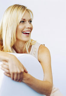 A smiling woman shows how our Cosmetic Dentist in Seattle, WA uses scaling & root planing for patients with gum disease.