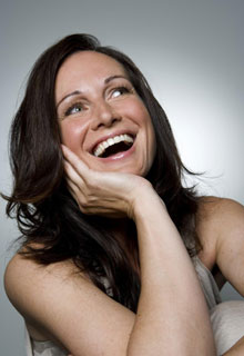 A woman laughs and smiles to illustrate how our Seattle cosmetic dentist experts make beautiful smiles.